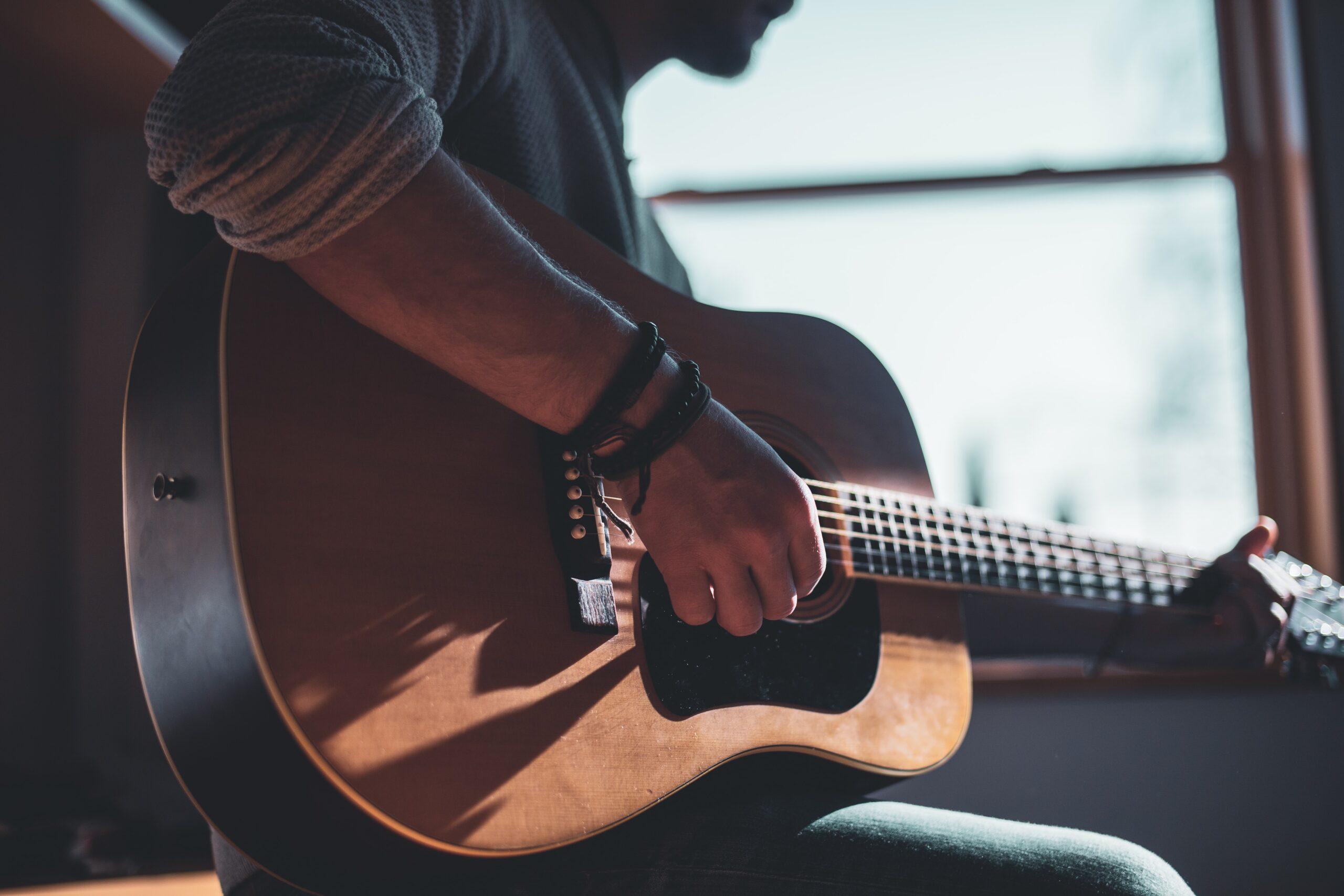 Kille som spelar gitarr